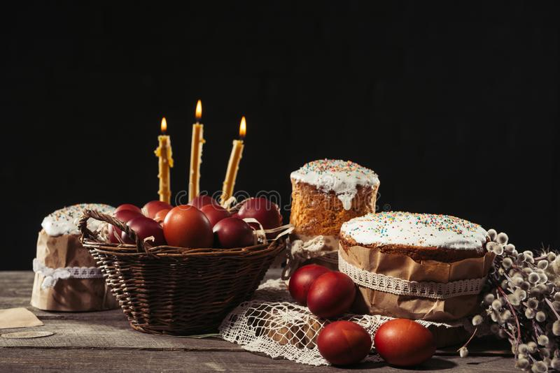 View of painted eggs in basket, willow twigs and delicious easter cakes. Burning candles, painted eggs in basket and tasty easter cakes on black royalty free stock image