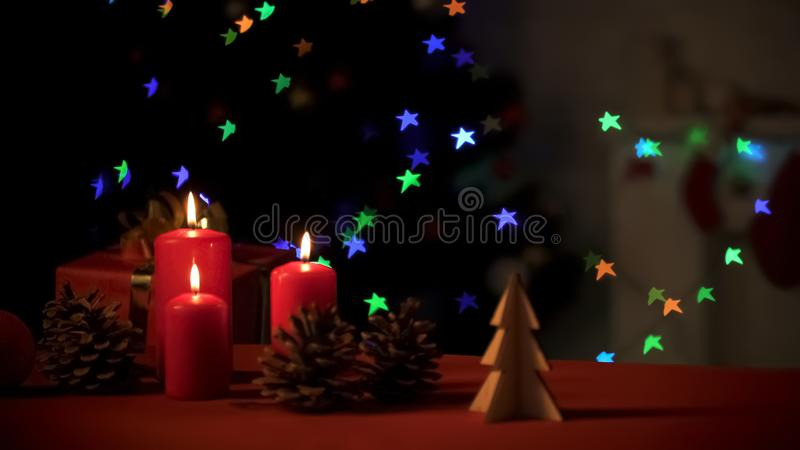 Burning candles with pines and wooden decorations standing on bright background stock photos