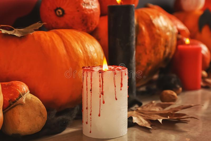 Burning candles with pumpkins prepared for Halloween party on floor stock image
