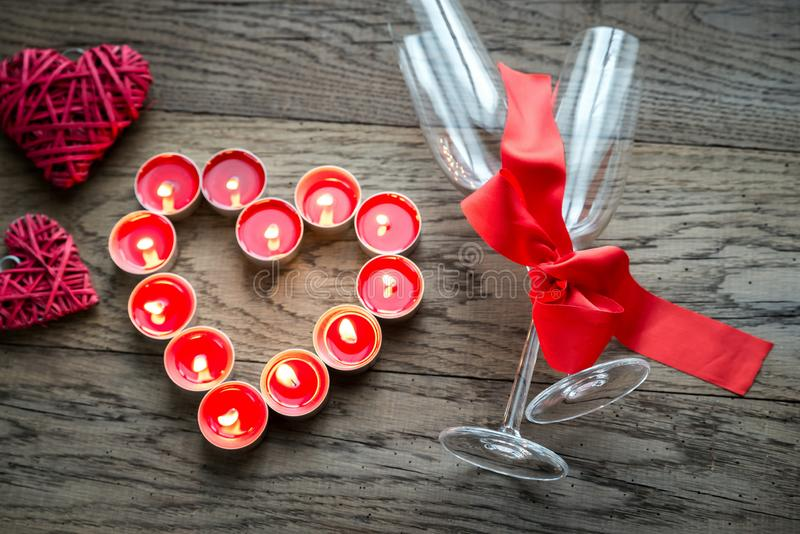 Burning candles in the shape of heart with two flutes royalty free stock images