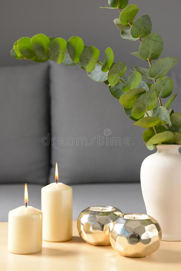 Burning candles and vase with eucalyptus branches on wooden table stock photos