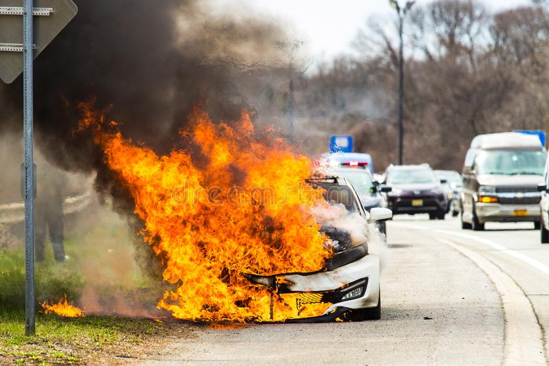 Burning car on fire on a highway road accident royalty free stock image