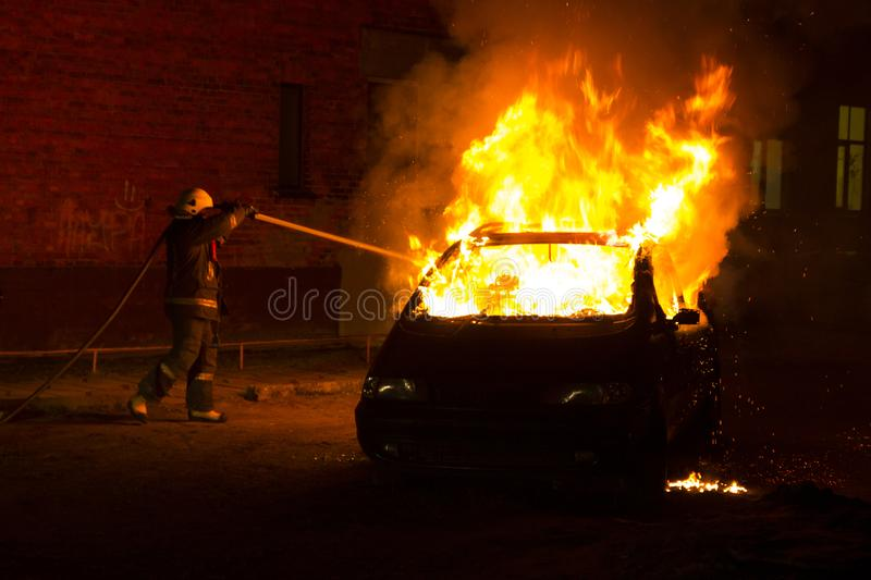 Burning car on the road in the night. Fire fighters at work stock photos