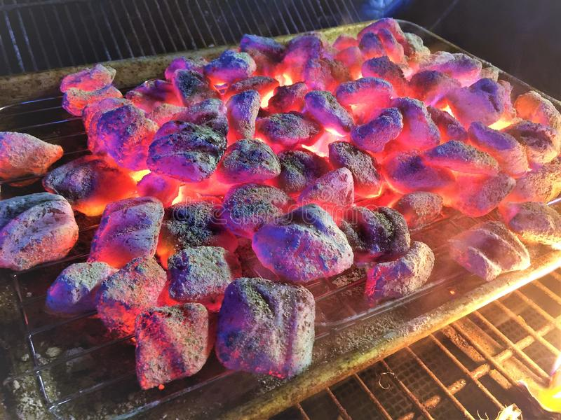 Burning Charcoal Briquettes. Ready to grill on a rack for BBQ and Grilling royalty free stock images