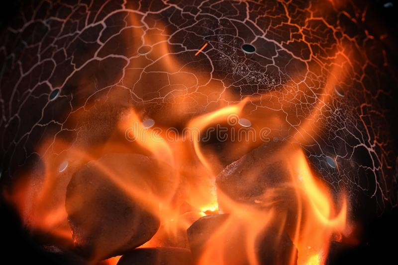 burning charcoal briquettes with red flames in a barbecue chimney starter, fire background with copy space royalty free stock photo