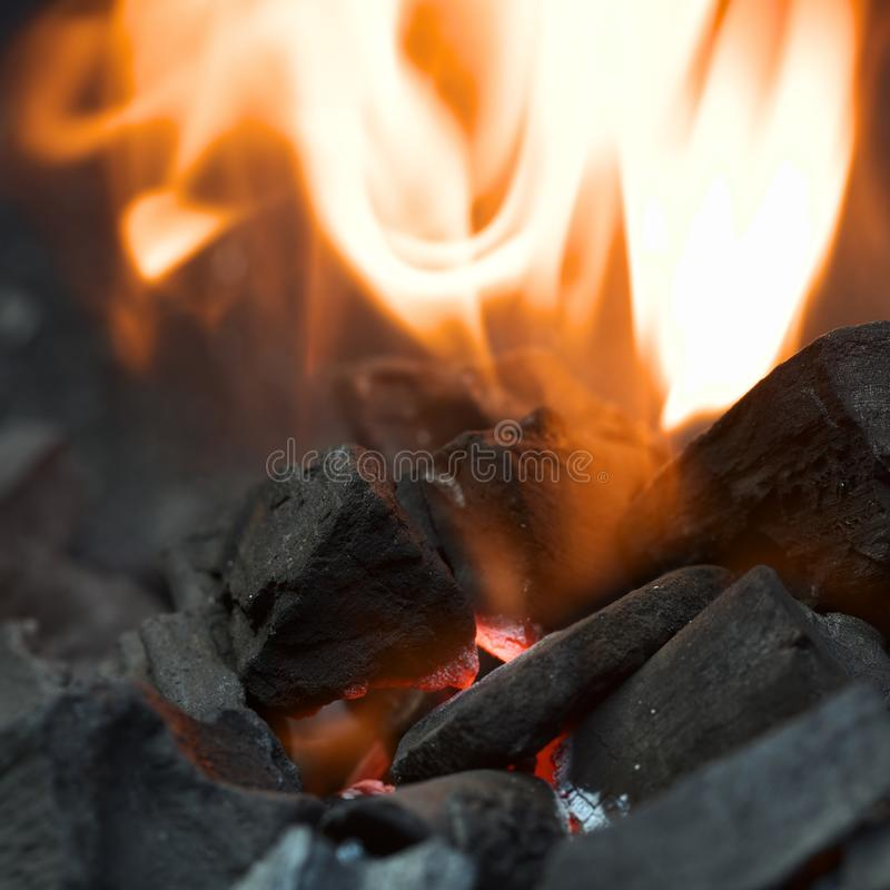 Burning Charcoal with Flames. Burning charcoal with orange-colored flame and glow Selective Focus, Focus on the front of the charcoal piece on the left side of stock photos