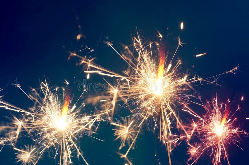 Burning christmas sparkler on blue background stock photos