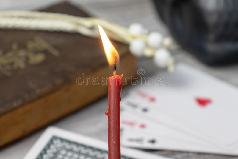 Burning church red candle in focus, blurred old holy bible, black skull and cards on wooden table. Misticism and fortune telling,. Future prediction concept stock photography