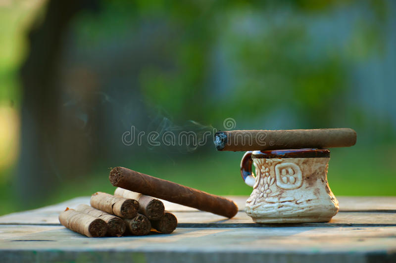 Burning cigar and coffee royalty free stock photo
