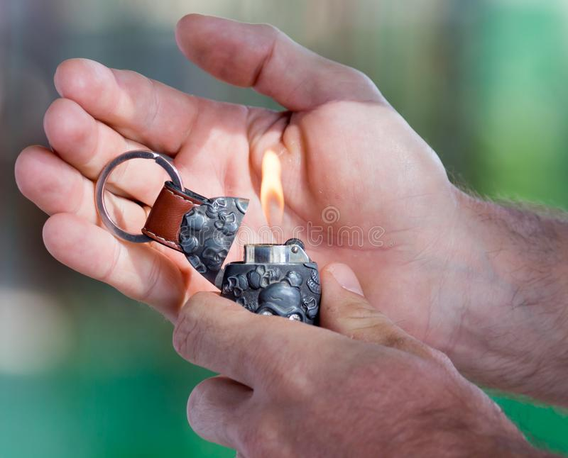 Burning cigarette lighter in his hand royalty free stock photo
