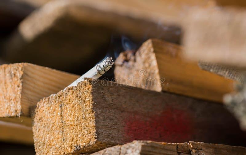 Burning cigarette on pine wood boards, conceptual human negligence image. Close up macro shot stock image