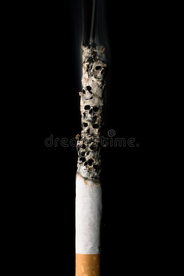 Burning cigarette with skulls and ash stock photography