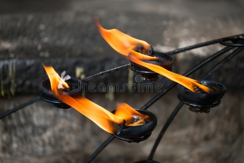 Burning clay oil lamp with bright fire in a temple. Burning clay oil lamp offerings with bright fire in a temple royalty free stock image