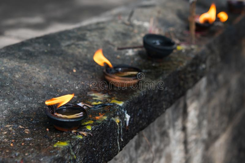 Burning clay oil lamp with bright fire in a temple. Burning clay oil lamp offerings with bright fire in a temple royalty free stock photos