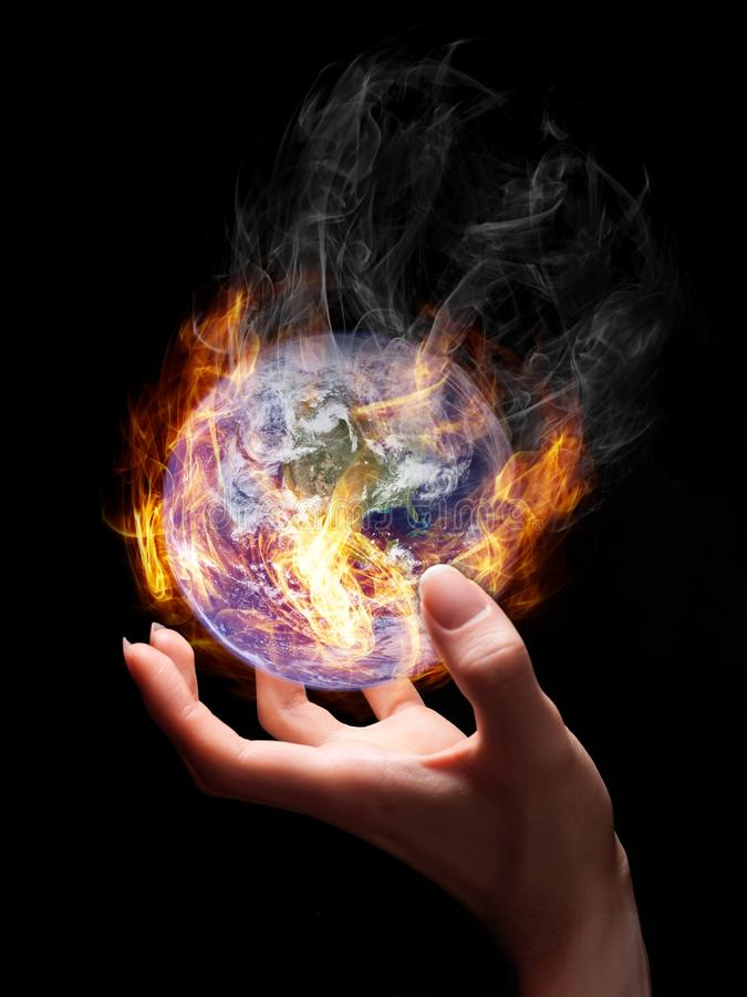 Burning Earth. Man holding burning Earth in his hand as a symbol of global warming or an apocalypse. Earth globe image provided by NASA stock photos