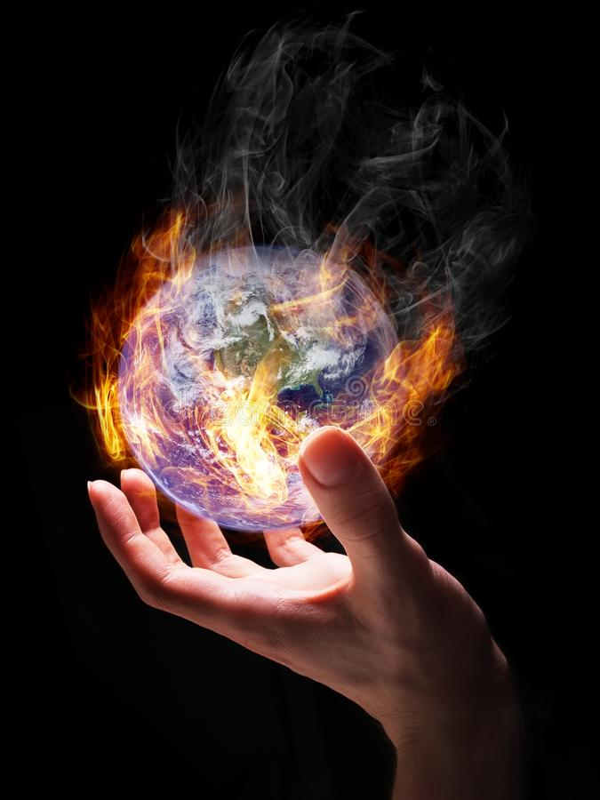 Burning earth. Man holding burning Earth in his hand as a symbol of global warming or an apocalypse. Earth globe image provided by NASA royalty free stock photos