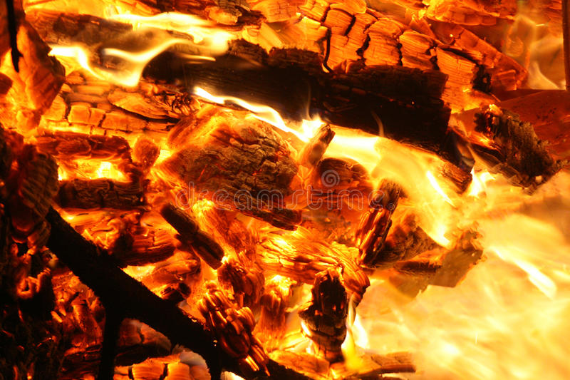 Burning fire. Fire burning with long and convoluted flames on consumed wood royalty free stock photos