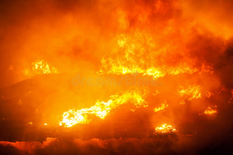 Burning fire flame on wooden house roof. Arson or nature disaster - burning fire flame on wooden house roof stock photo