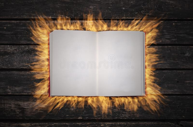 Magic book. Burning with fire an open magic book with empty blank pages on the table stock images
