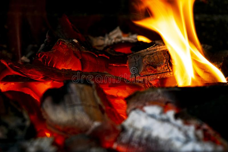 Burning firewood in the fireplace close up, BBQ fire, charcoal background. Charcoal fire with sparks. Fire background. Close up. Burning firewood in the stock images