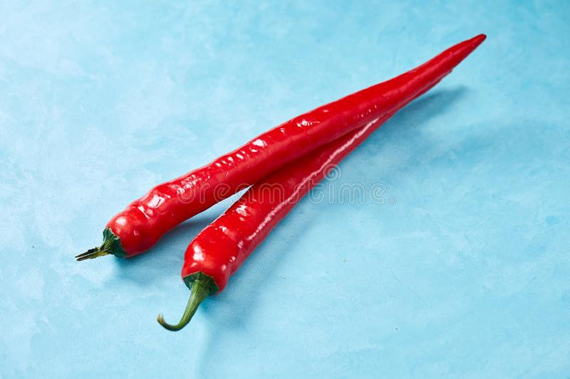 Burning fresh red hot pepper on a blue background, top view, close-up royalty free stock photo