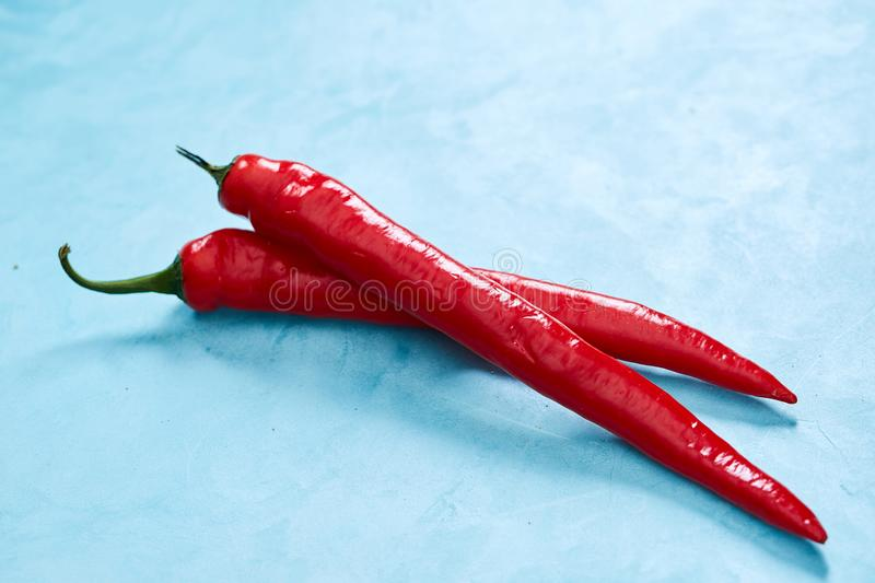 Burning fresh red hot pepper on a blue background, top view, close-up royalty free stock photography