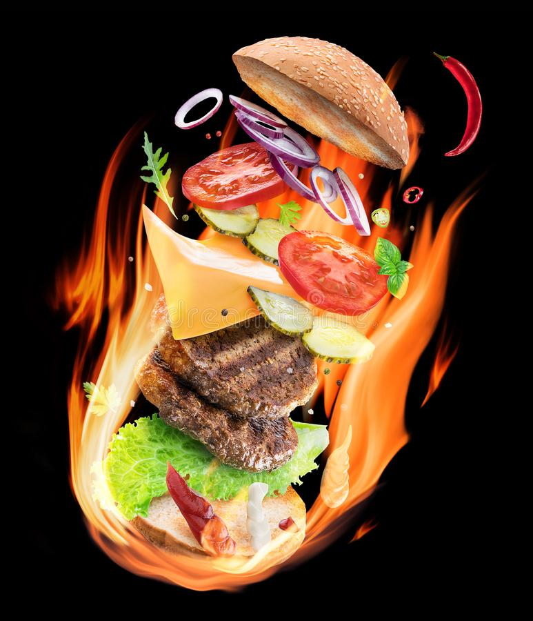 Burning hamburger ingredients in flames on the black background royalty free stock photo