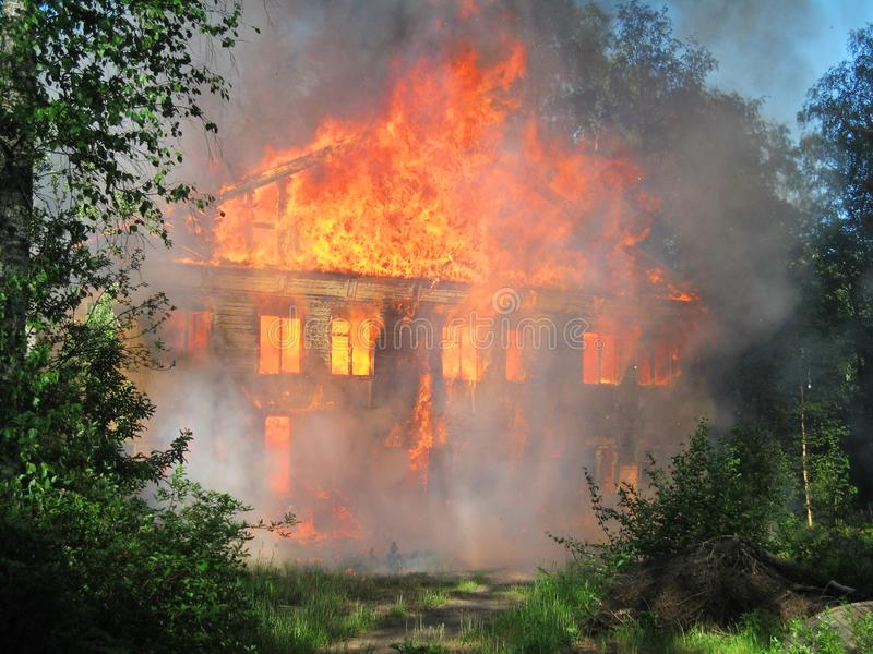 Burning house. Big wooden building completely destroyed by fire royalty free stock photography