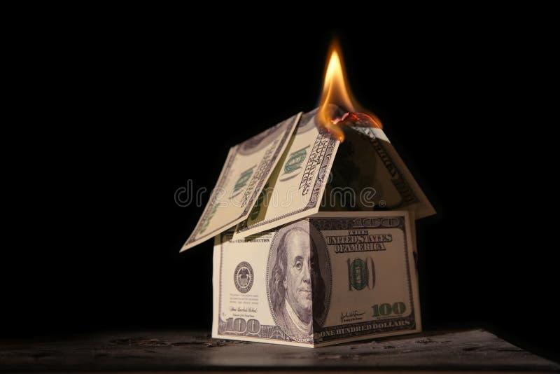 Burning house of dollars. On black stock images
