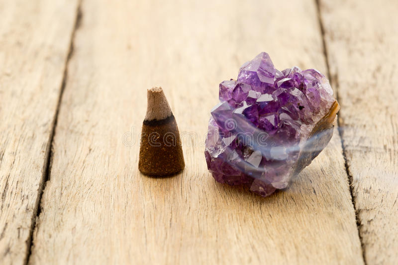 Burning incense cone with amethyst crystal with wafting smoke on royalty free stock image