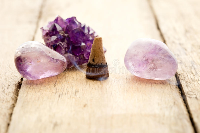 Burning incense cone with amethyst crystals with wafting smoke o stock photos