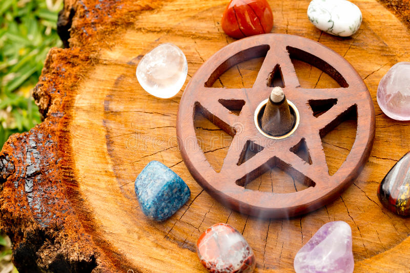 Burning incense cone in wooden pentacle incense holder on natur stock photo