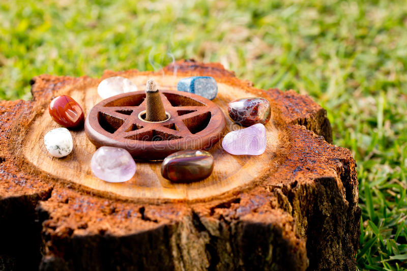 Burning incense cone in wooden pentacle incense holder on natur royalty free stock image