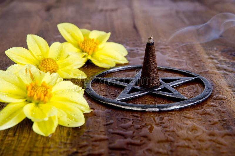 Burning incense in metal pentagram with yellow dahlia flowers on stock image