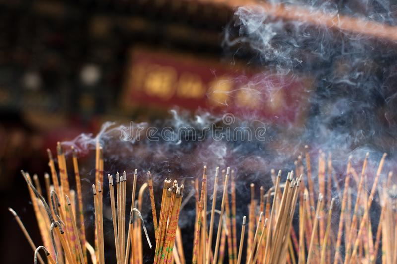 Burning incense stick at the temple. Hundreds of prayer incense stick burned at the temple`s altar with smoke stock photos