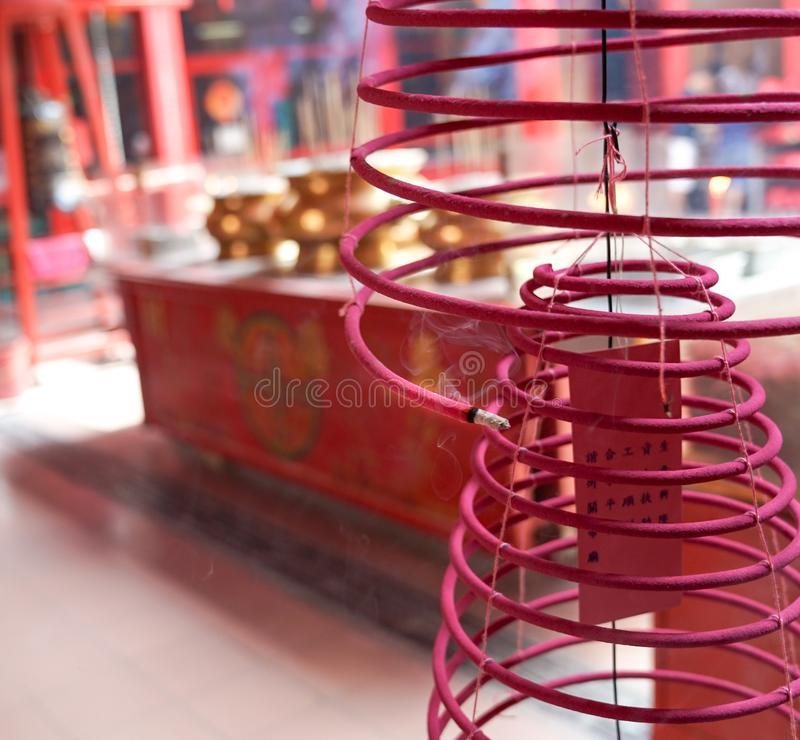 Burning incense in a taoist temple. Red burning incense in a taoist temple with copy space royalty free stock images