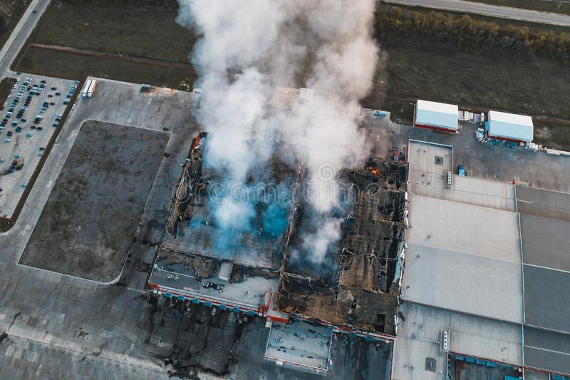 Burning industrial building with fire, huge thick smoke and burnt roof, aerial view stock images