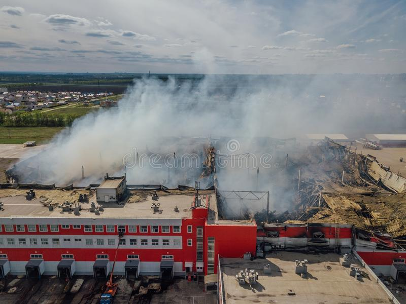 Burning industrial distribution warehouse, aerial drone view.  royalty free stock photo