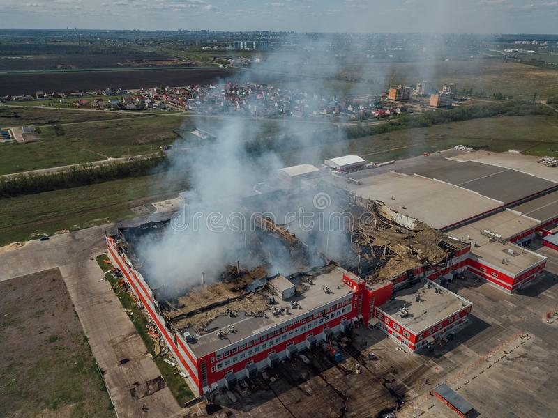 Burning industrial distribution warehouse, aerial drone view.  royalty free stock photos