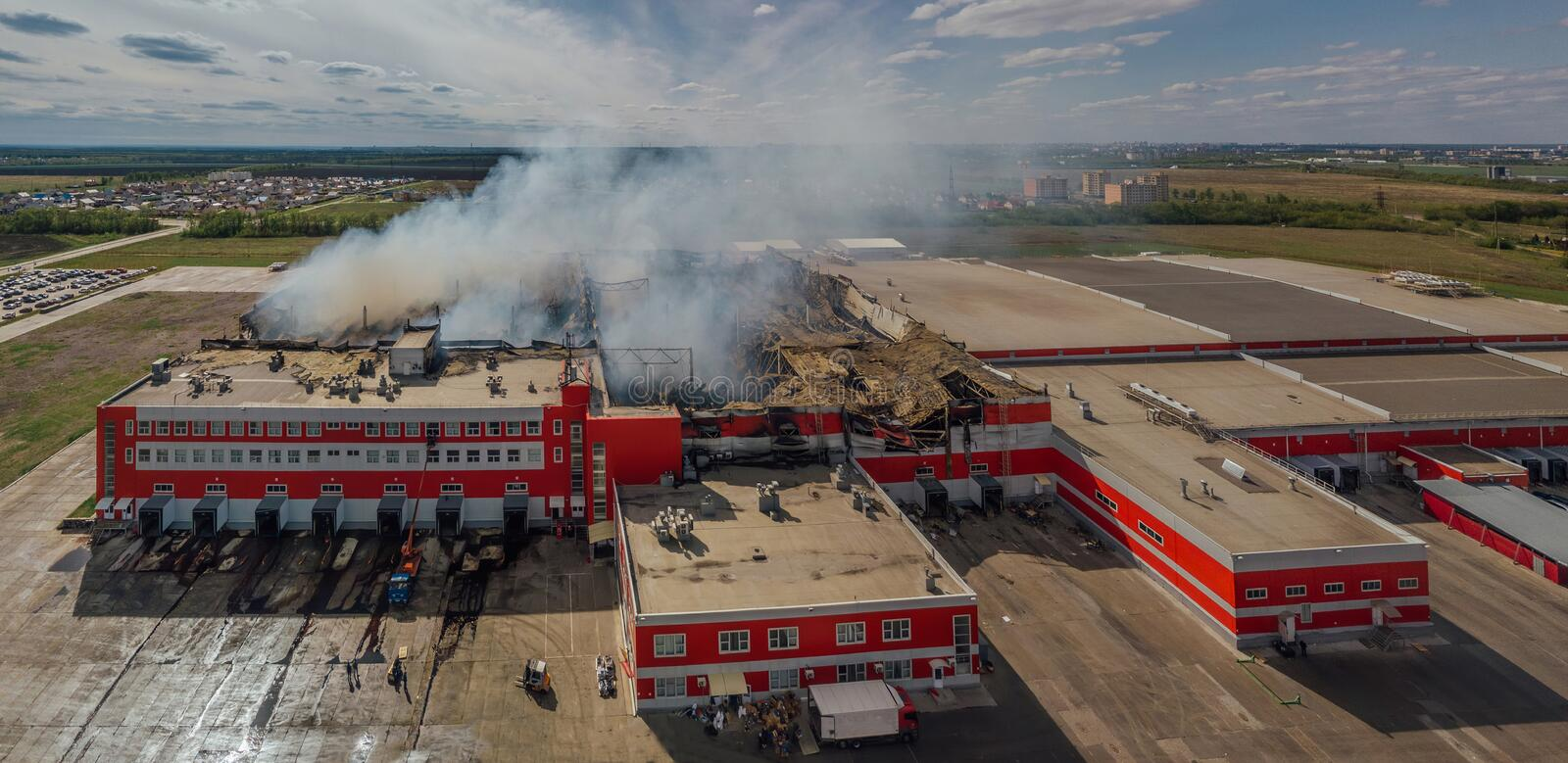 Burning industrial distribution warehouse, aerial drone view.  royalty free stock images