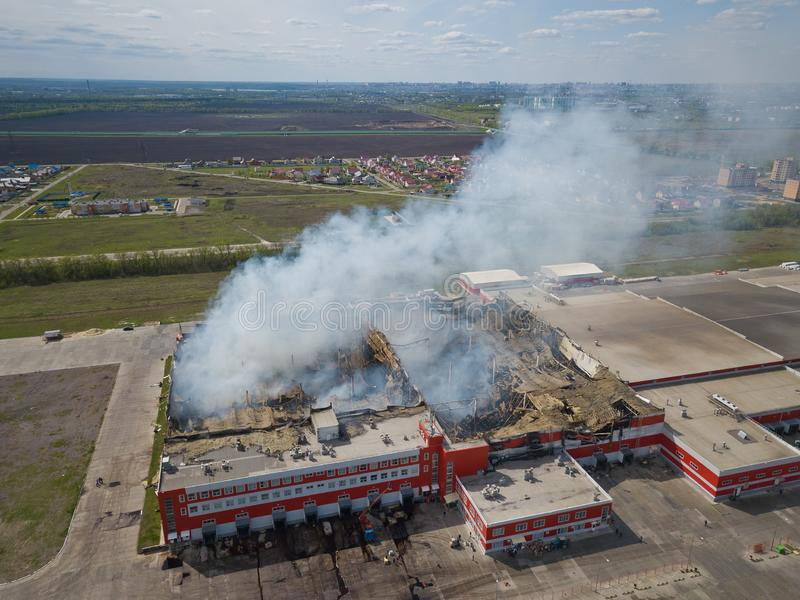 Burning industrial distribution warehouse, aerial drone view.  stock photos