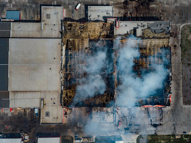 Burning industrial distribution warehouse, top view from drone.  stock photography