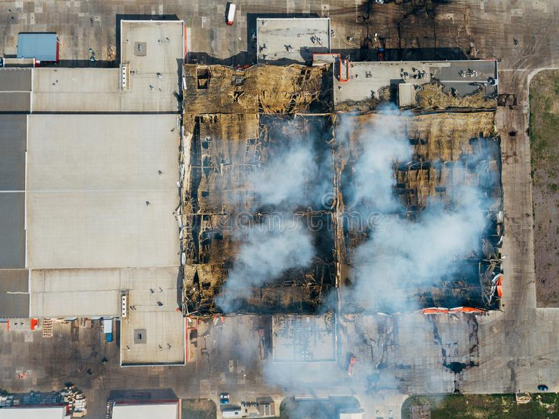 Burning industrial distribution warehouse, top view from drone.  stock images