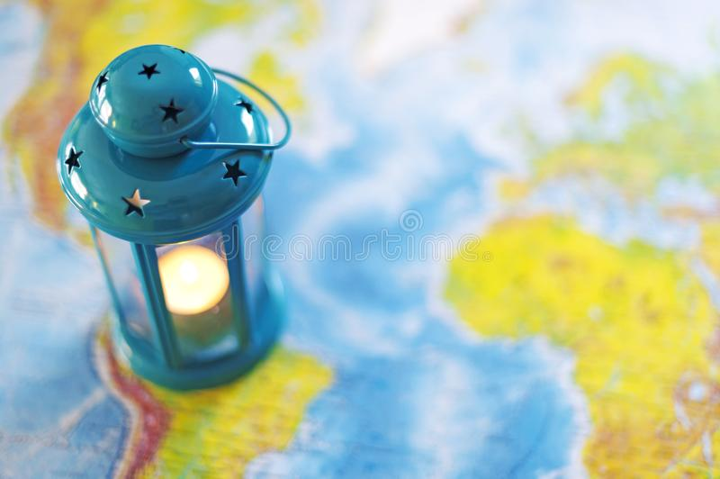 The burning lamp is blue On the map. Inside the lamp, the candle is burning white royalty free stock image