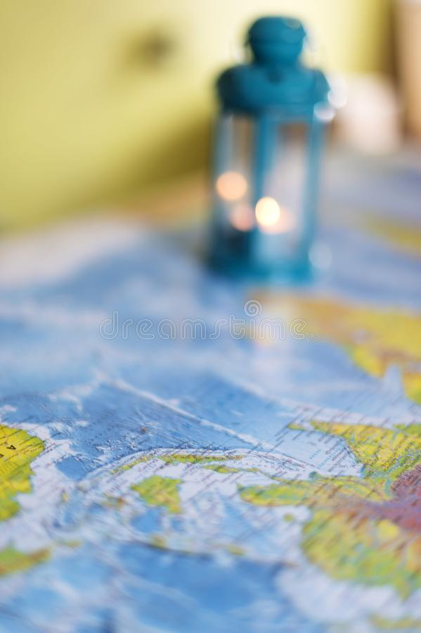The burning lamp is blue On the map. Inside the lamp, the candle is burning white stock image