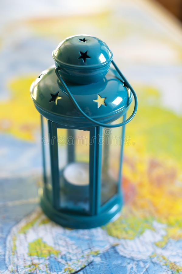 The burning lamp is blue On the map. Inside the lamp, the candle is burning white royalty free stock photos