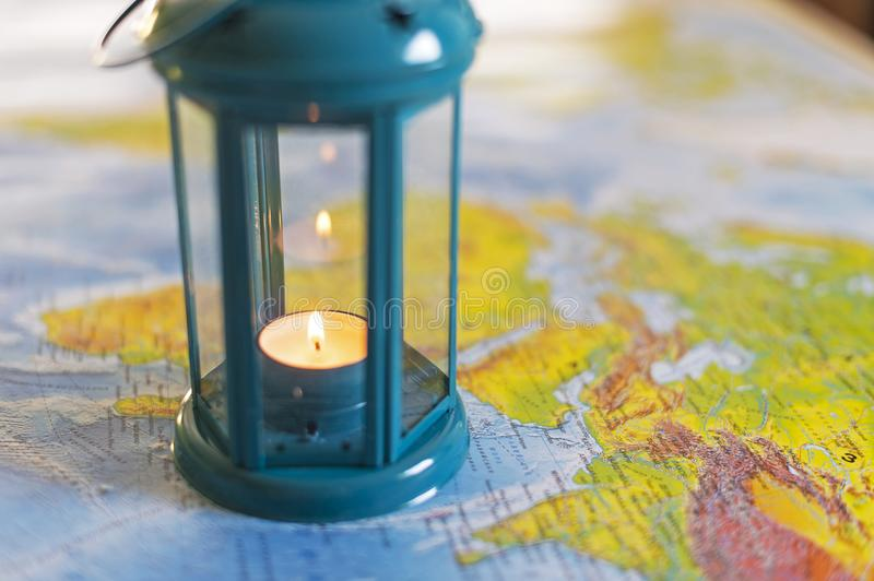 The burning lamp is blue On the map. Inside the lamp, the candle is burning white royalty free stock photo