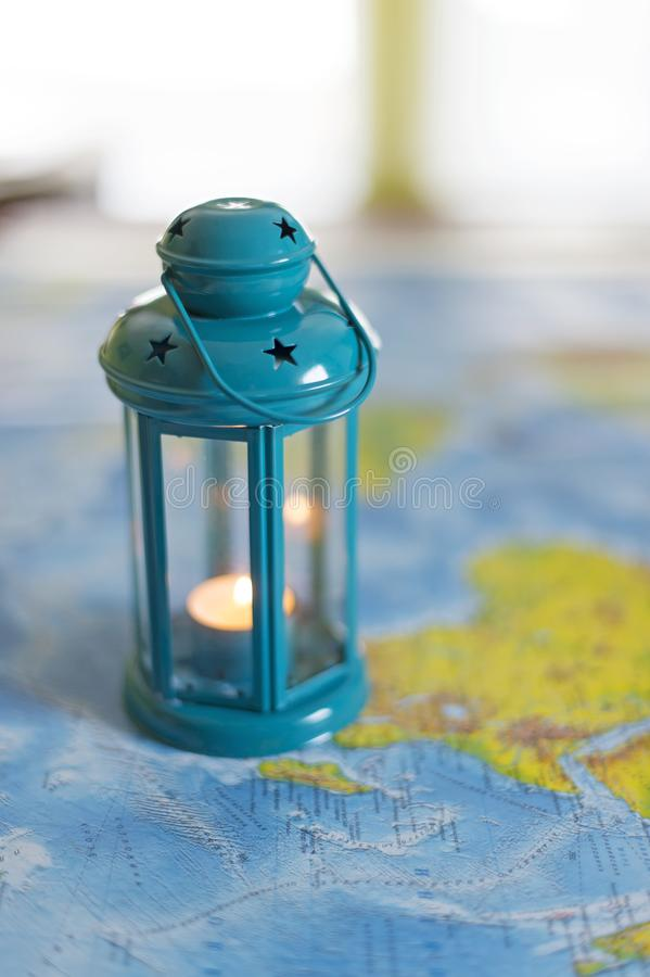 The burning lamp is blue On the map. Inside the lamp, the candle is burning white royalty free stock photography