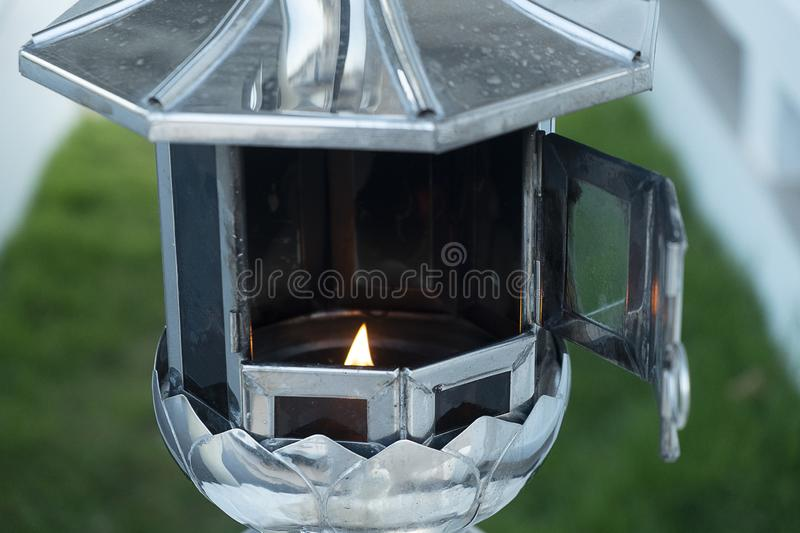 Burning lantern candles frame on the altar of Buddha in church or temple, Buddhists make merit stock photography