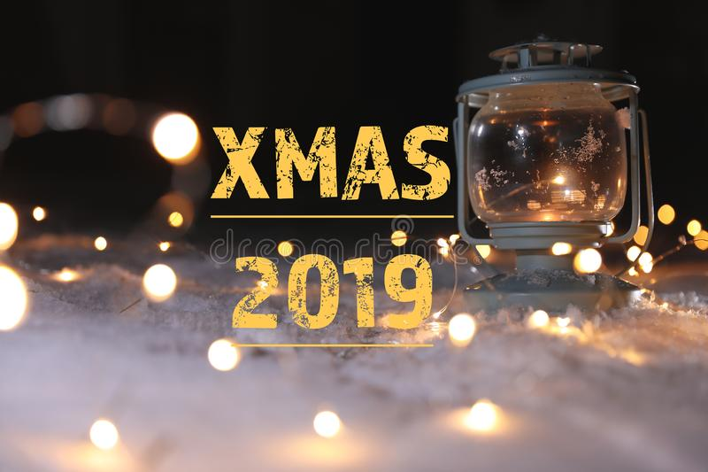 Burning lantern with Christmas lights on snow and message XMAS 2019 against dark background. stock photos